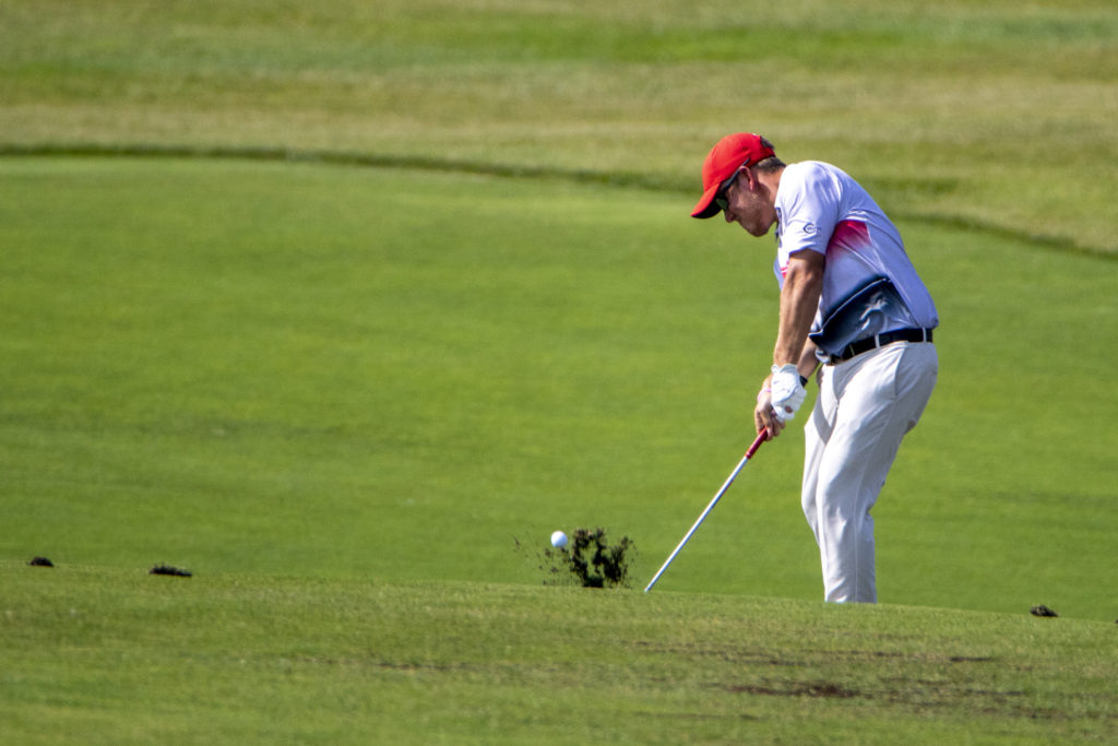 Man hitting golf ball in a golf tournament.