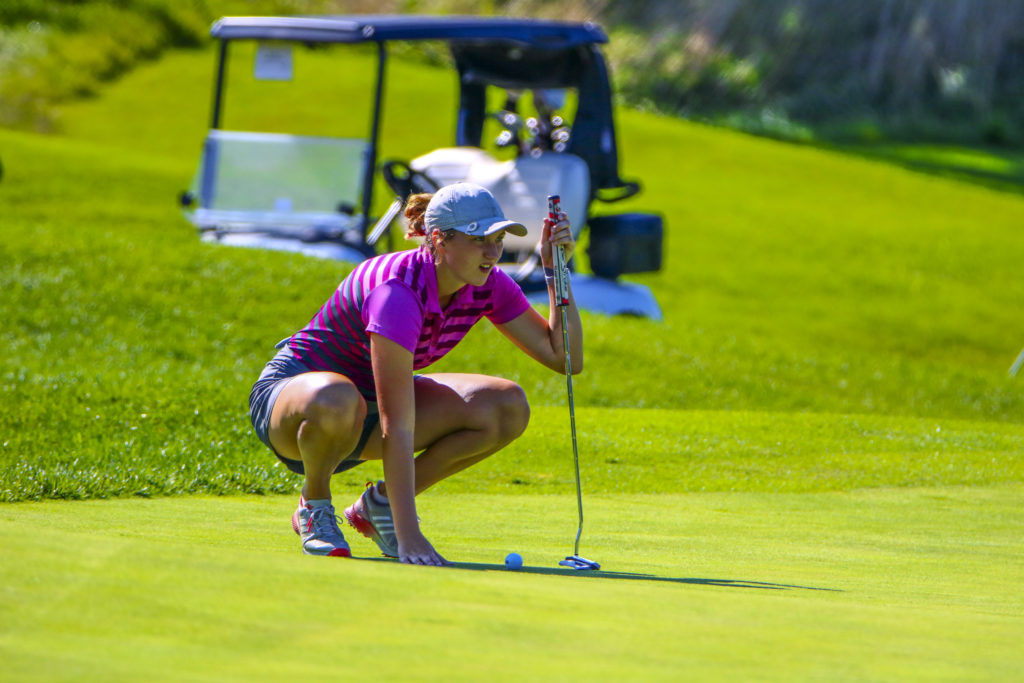 Woman looking at her putting line on putting green.